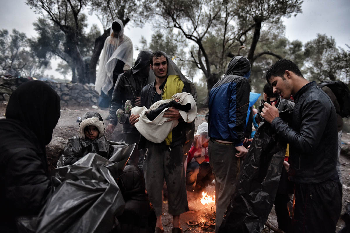 Migrants wait under an heavy rain, outside the Moria registration camp, on October 23, 2015, on the Lesbos island. Many Syrian families with small children are currently forced to walk a distance longer than the Athens Marathon from the beaches where they land to the points of registration near the port capital of Mytilene. Buses provided by local authorities and rides by volunteers do not suffice, especially as many refugees continue to land at night. Over 400,000 people have landed on Greek islands from neighbouring Turkey since the beginning of the year, most of them fleeing the civil war in Syria. AFP PHOTO / ARIS MESSINIS / AFP PHOTO / ARIS MESSINIS