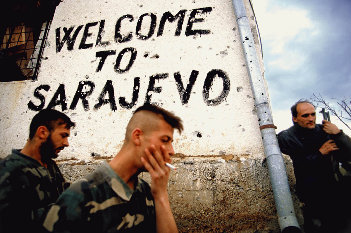 Bosnian soldiers smoke and take a break on the frontline next to a sign that says 'welcome to Sarajevo' in Sarajevo, Bosnia, in the fall of 1994.  Trench warfare was fought all around the city of Sarajevo.