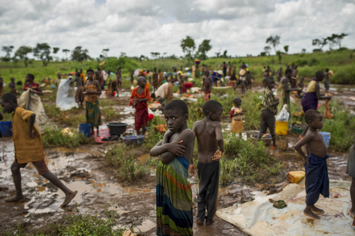 "A Burundian refugee is pictured as others wash clothes near a river on the edge of the Nyarugusu refugee camp in Tanzania on March 26, 2016. According to UNHCR, Nyarugusu is ""one of the largest and most overcrowded refugee camps in the world"", currently hosting over 140,000 refugees but built to accommodate only 50,000. The camp has a resident population of around 60,000 Congolese refugees, with an influx of around 78,000 Burundian refugees since last year."