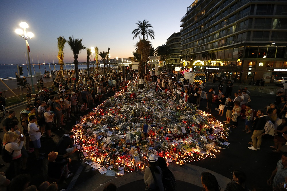 People gather at a makeshift memorial on the Promenade des Anglais in Nice on July 17, 2016, in tribute to the victims of the Bastille Day attack that left 84 dead. The Islamic State group claimed responsibility for the truck attack that killed 84 people in Nice on France's national holiday, a news service affiliated with the jihadists said on July 16. Tunisian Mohamed Lahouaiej-Bouhlel, 31, smashed a 19-tonne truck into a packed crowd of people in the Riviera city celebrating Bastille Day -- France's national day. / AFP PHOTO / Valery HACHE