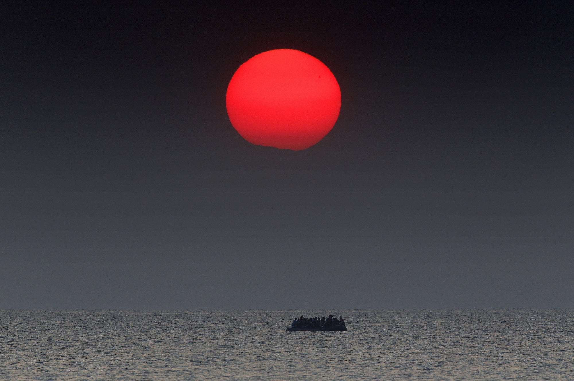 As the sun rises a dinghy overcrowded with Syrian refugees drifts in the Aegean sea between Turkey and Greece after its motor broke down while traveling from the Turkish coast to the Greek island of Kos, August 11, 2015. A Greek coast guard responded to distress signals and arrived at the scene to help. REUTERS/Yannis Behrakis